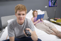 Hållande ögonen på TV för ung man i sovrum Fotografering för Bildbyråer