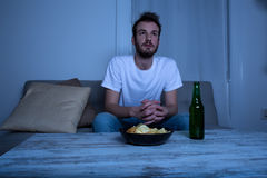 Hållande ögonen på TV för ung man på nattetid med chiper och öl Arkivfoton