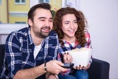 Hållande ögonen på TV för unga lyckliga par hemma Arkivbilder