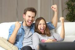 Hållande ögonen på tv för upprymda par hemma Arkivbilder