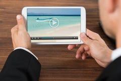 Hållande ögonen på video för Businessperson på mobiltelefonen Arkivfoto