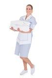Hållande handdukar för lycklig ung hembiträde Arkivfoto