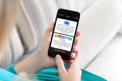 Hållande iPhone 6 för kvinna med den Apple lön och bankboken Arkivfoto