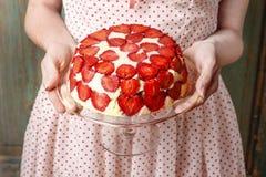 Hållande jordgubbekaka för kvinna på kakaställning Royaltyfri Foto