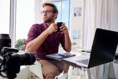 Hållande kaffe för ung fotograf på hans hem- studio Royaltyfri Bild