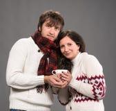 Hållande kopp kaffe för par på en grå bakgrund Fotografering för Bildbyråer