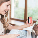 Hållande kreditkort för härlig lyckad kvinna och shopping till och med bärbara datorn Arkivbild