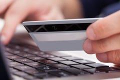 Hållande kreditkort för person genom att använda bärbara datorn Arkivbilder