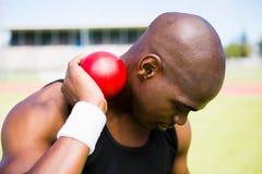 Hållande kulstötningboll för manlig idrottsman nen Royaltyfria Foton