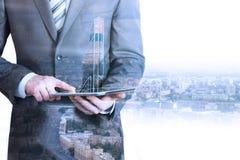 Hållande minnestavla för affärsman med modellen för stad 3d Arkivbild