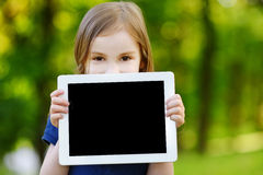 Hållande minnestavlaPC för lyckligt barn utomhus Royaltyfria Bilder