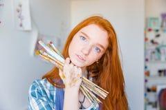 Hållande målarpenslar för härlig eftertänksam målare för ung kvinna i konststudio Arkivbild