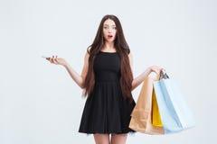 Hållande mobiltelefon- och shoppingpåsar för förvirrad häpen kvinna Royaltyfri Foto