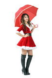 Hållande paraply för härlig jultomtenhjälpredaflicka som ler och ser kameran Arkivfoton