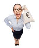 Hållande pengarpåse för häpen affärskvinna med euro Royaltyfria Bilder