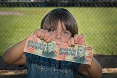Hållande pengarsedlar för litet barn Fotografering för Bildbyråer