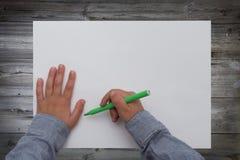Hållande penna för barn på det tomma arket av papper Fotografering för Bildbyråer