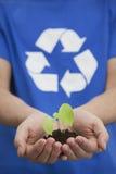 Hållande planta för ung man i hans händer, återvinningsymbol, slut upp Arkivbild