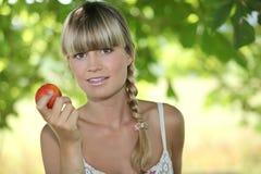 Hållande äpple för blond kvinna Arkivbilder