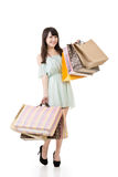 Hållande shoppingpåsar för attraktiv asiatisk kvinna Royaltyfri Bild