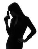 Hållande siktande vapensilhouette för sexig detektiv- kvinna Arkivfoto