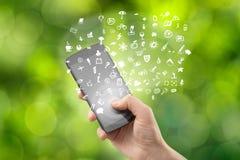 Hållande smartphone för hand med symboler Arkivbild