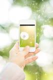 Hållande smartphone för kvinna med blomman Royaltyfria Bilder