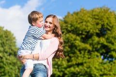 Hållande son för moder i armar som kysser honom Royaltyfri Fotografi