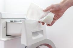 Hällande tvättmedel in i tvagningen bearbetar med maskin Royaltyfri Foto