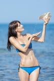 Hällande vatten för flicka från skal Arkivfoto