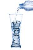 hällande vatten i ett elegant högväxt exponeringsglas med is- och vattendroppar Arkivfoton