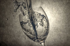 Hällande vatten till vinrankaexponeringsglas Royaltyfri Foto