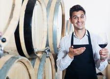 Hällande vin för säljare i källare Arkivfoto