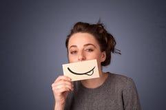 Hållande vitt kort för nätt ung flicka med leendeteckningen Fotografering för Bildbyråer