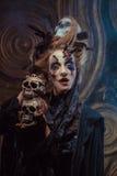 Hloding Schädel der jungen Hexe Hell bilden Sie und rauchen Sie Halloween-Thema Stockfotos