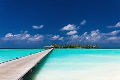 Hölzerne Anlegestelle zu einer Tropeninsel über Lagune in Malediven Lizenzfreies Stockbild