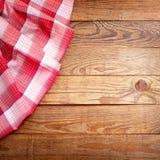 Hölzerne Beschaffenheit, Holztisch mit Draufsicht des roten Tischdeckenschottenstoffs Stockfotografie
