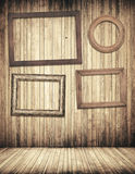 Hölzerne Bilderrahmen, die an der braunen Plankenwand hängen Stockfotos