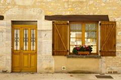 Hölzerne Blendenverschlüsse und Blumen Cajarc der Fassade Lizenzfreies Stockfoto