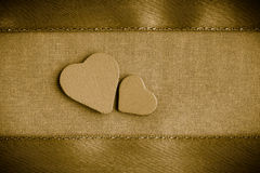 Hölzerne dekorative Herzen des Valentinsgrußes auf goldenem Stoffhintergrund Lizenzfreie Stockbilder