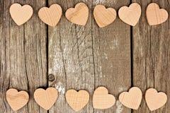 Hölzerne Herzen, die eine doppelte Grenze gegen rustikales Holz bilden Lizenzfreie Stockfotos