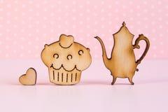 Hölzerne Ikonen des Kuchens und der Teekanne mit wenig Herzen auf rosa backgr Stockbild