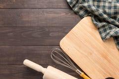 Hölzerne Küchenwerkzeuge und -serviette auf dem hölzernen Hintergrund Lizenzfreie Stockfotografie