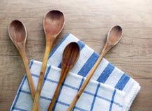 Hölzerne kochende Löffel und Baumwollgeschirrtücher auf dem Tisch Lizenzfreie Stockfotos