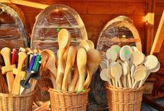 Hölzerne Löffel, Küchengeräte und hölzerne Trainingsklingen in den Weidenkörben Stockbild