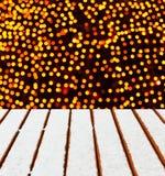 Hölzerne Plattform mit Schnee- und Weihnachtslichthintergrund. Lizenzfreie Stockbilder
