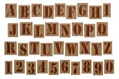 Hölzerne Schmutzalphabetbuchstaben und -zahlen Stockbild