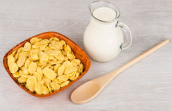 Hölzerne Schüssel mit Corn Flakes, Krug Milch und Löffel Lizenzfreies Stockfoto