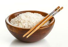Hölzerne Schüssel mit Reis und Essstäbchen Lizenzfreies Stockfoto