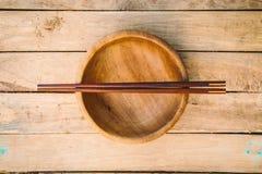 Hölzerne Schüsseln und hölzerne Essstäbchen auf Holz Stockbild